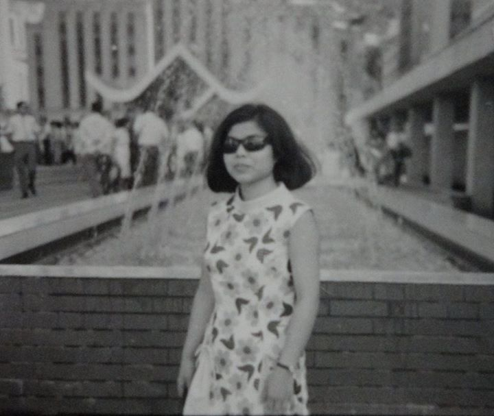 Black and white photo of my mom, wearing shades, standing in front of fountain