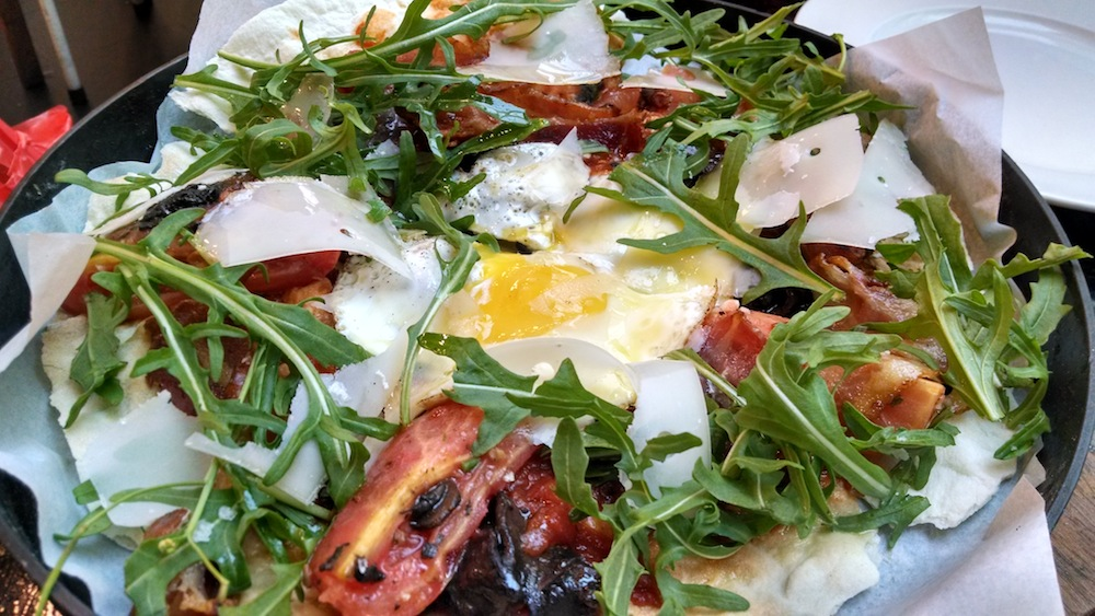 Pizza with bacon, cheese shavings, arugula or rocket, and egg in the middle