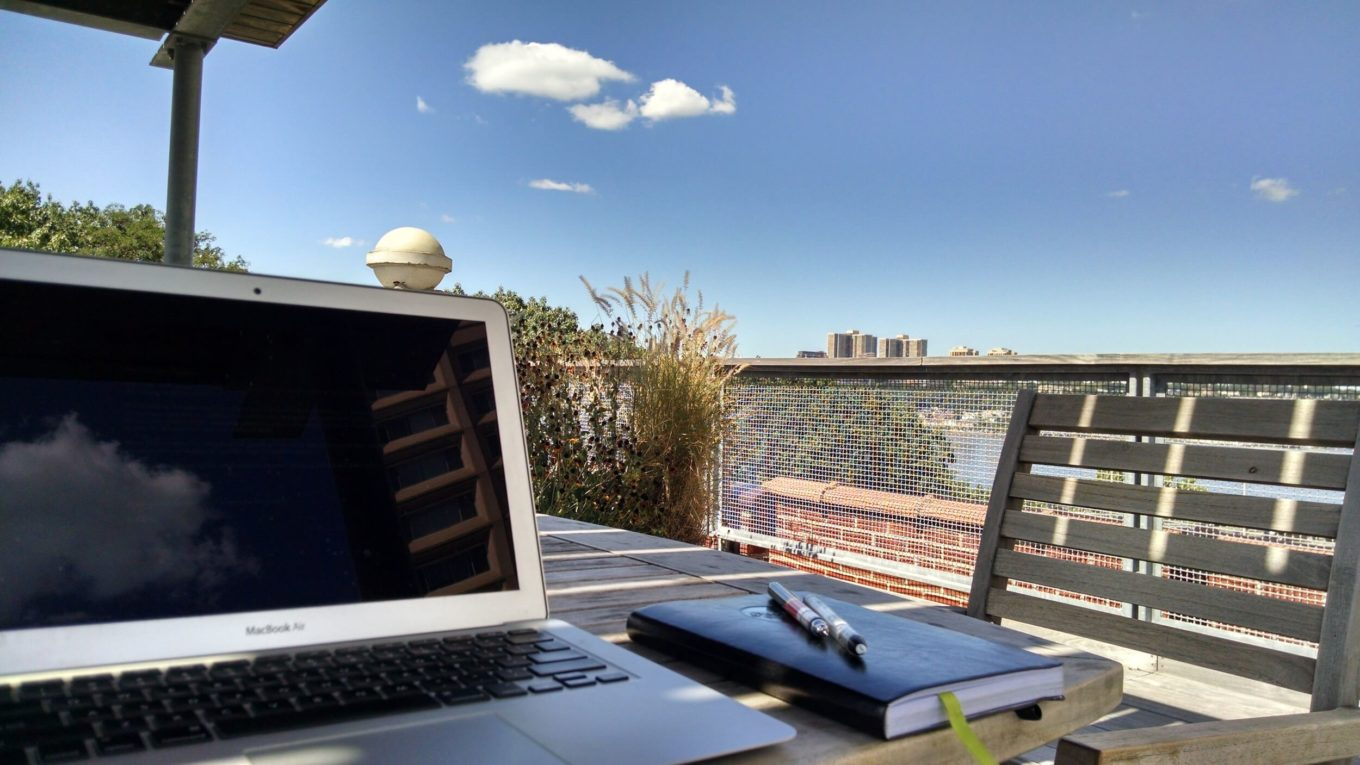 Laptop on table with sky in background